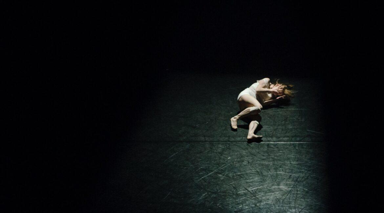 Um palco escuro, somente um ponto é iluminado. Nesse ponto tem uma pessoa deitada meio de lado, com as mãos na cabeça.