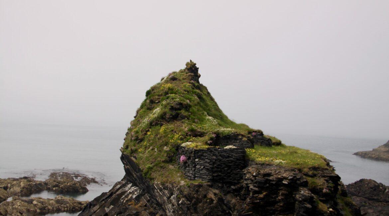 um pico de montanha de pedras, verde por cima. observa-se o mar ao fundo